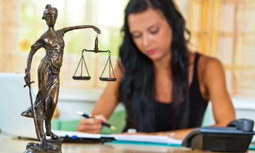 Eine erfolgreiche Rechtsanwältin im Büro mit Justitia Figur im Vordergrund.